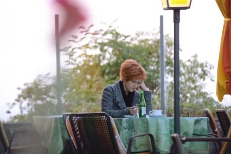 Auf der hinteren Terrasse sitzt eine Frau.